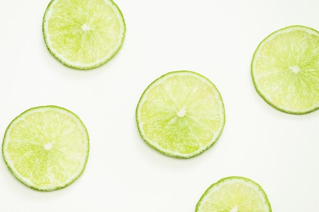 Composition avec citron vert frais sur fond clair, vue de dessus, gros plan.