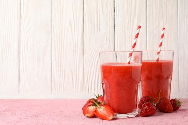 Composition avec des cocktails de fraises sur table rose. boisson d'été