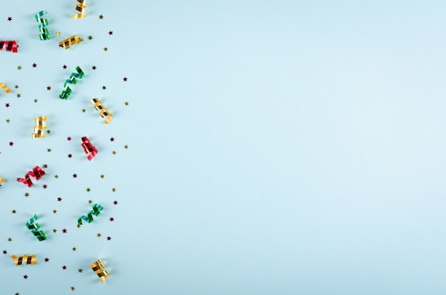 Composition colorée de confettis et ballons à air chaud sur fond bleu, décoration de fête et de célébration.