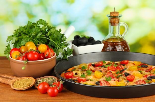 Composition colorée de délicieuses pizzas, légumes et épices sur bois