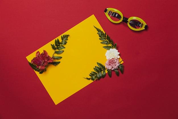 Composition colorée avec des fleurs et des lunettes tropicales