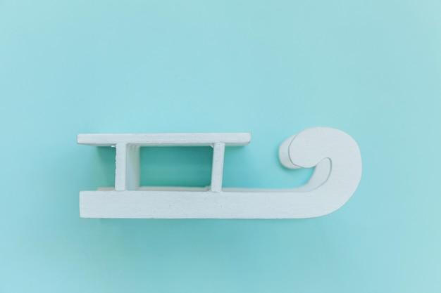 Composition de conception simplement minimale traîneau blanc isolé sur bleu pastel coloré