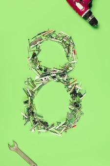 La composition conceptuelle d'un ensemble de clous, de vis et d'outils sur les vacances de la journée des femmes de huit mars sur fond vert. le chiffre 8 en déco. vue de dessus. les femmes dans les métiers masculins