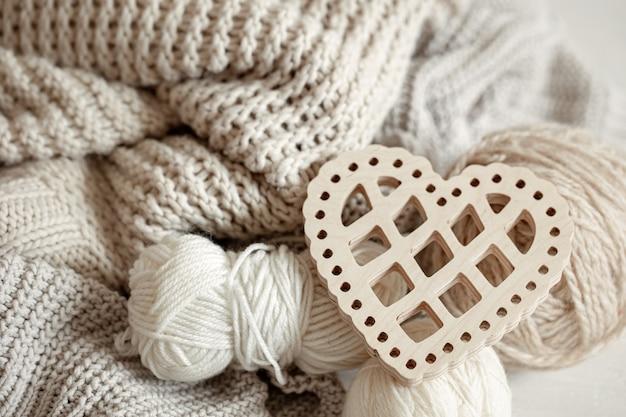 Composition confortable avec des articles tricotés et un coeur décoratif en bois se bouchent.