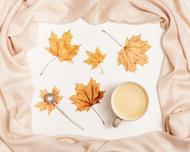 Composition confortable d'automne avec des feuilles séchées d'érable et une écharpe beige pastel et du café