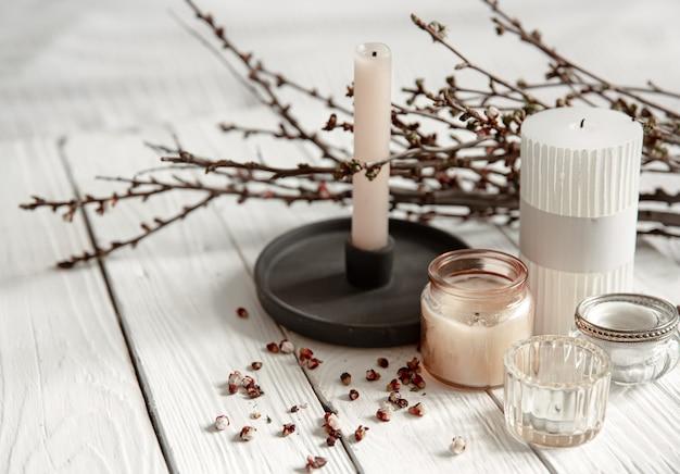 Composition confortable avec des bougies décoratives et des branches de jeunes arbres sur une surface en bois dans un style rustique.