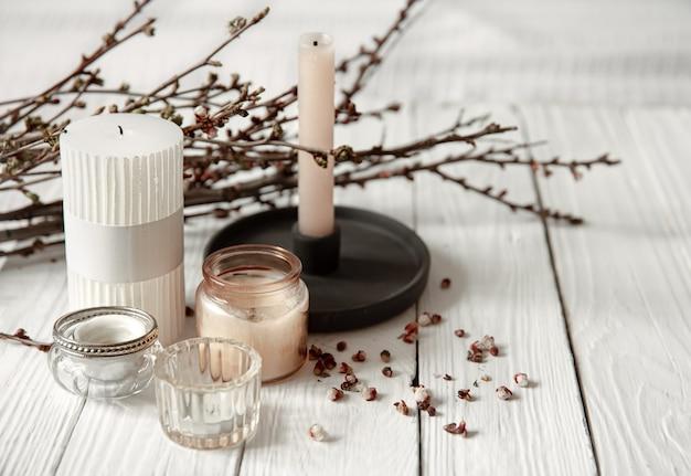 Composition confortable avec des bougies décoratives et de jeunes branches d'arbres sur une surface en bois dans un style rustique.