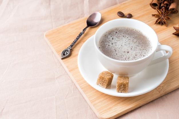 Composition confortable avec une tasse de café sur un plateau avec du sucre sur une couverture de café pastel plat poser, vue de dessus.