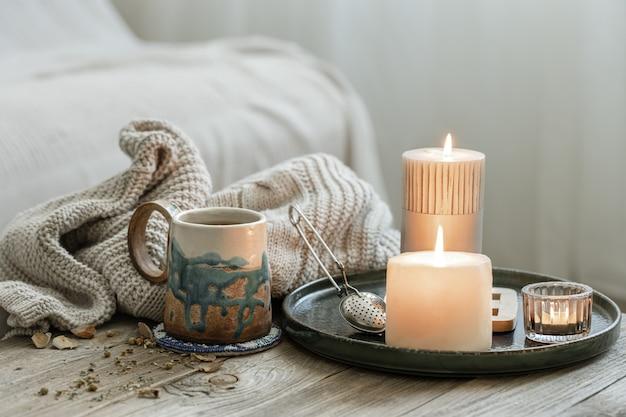 Composition confortable avec une tasse en céramique, des bougies et un élément tricoté sur fond flou.
