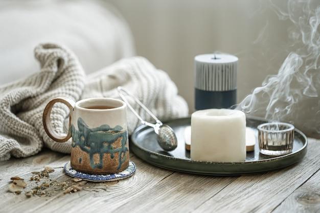 Composition confortable avec une tasse en céramique, des bougies et un élément tricoté