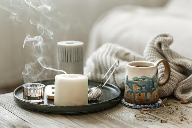 Composition Confortable Avec Une Tasse En Céramique, Des Bougies Et Un élément Tricoté Photo gratuit
