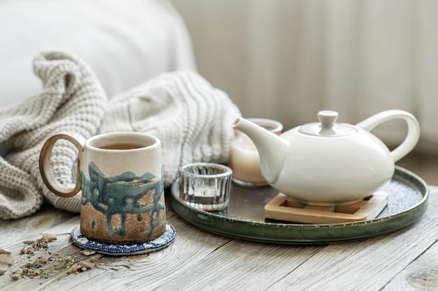 Composition confortable avec une tasse en céramique, une théière et un élément tricoté sur un fond flou.
