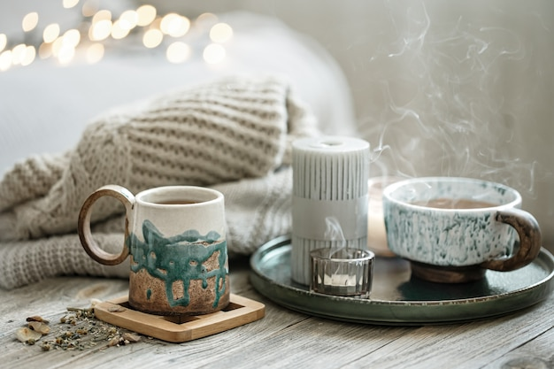 Composition confortable avec des tasses et des bougies en céramique sur un arrière-plan flou avec bokeh.