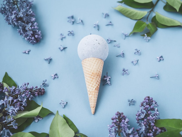 Composition de cornet de crème glacée avec boule de bain. lay plat. vue de dessus. fleurs lilas