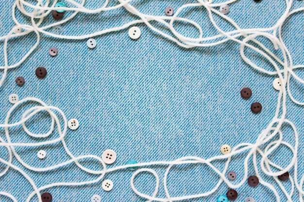 Composition de couture avec des boutons de ficelle blanche sur un tissu bleu