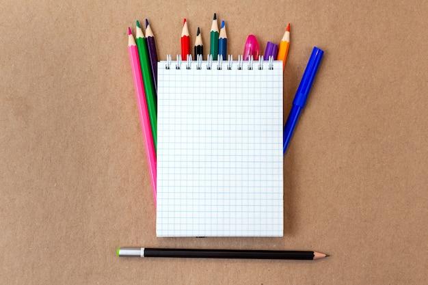 Composition avec un crayon coloré page blanche pour ordinateur portable, un marqueur et un stylo avec copie espace sur un fond en carton artisanal