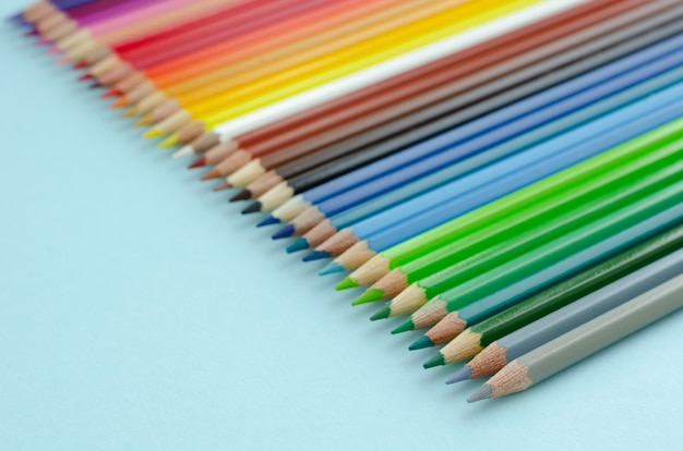 Composition de crayons de couleur sur fond bleu. lay plat.