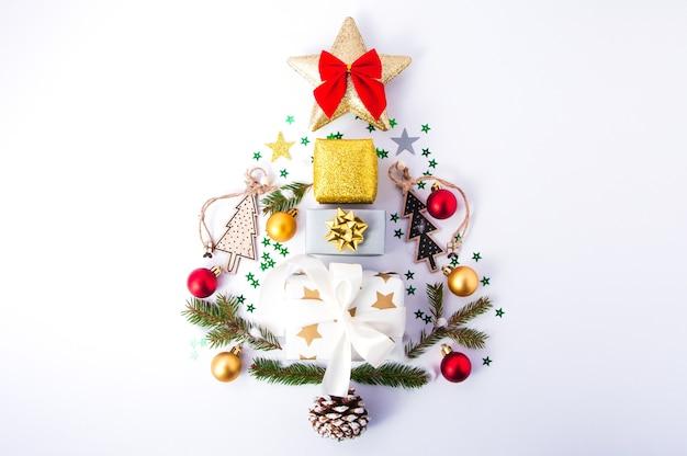 Composition créative de l'arbre de noël fait de décorations de noël sur la vue de dessus plat blanc