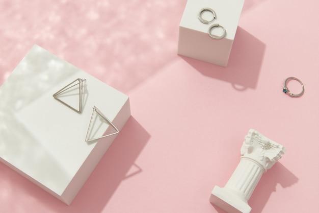 Composition créative avec bijoux en argent sur fond rose accessoires tendance dans un style minimaliste