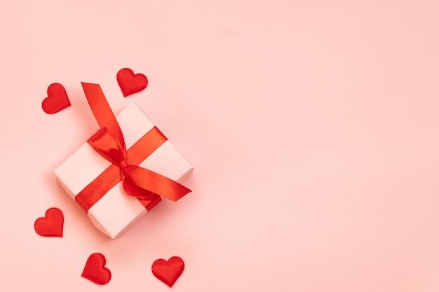 Composition créative de boîte-cadeau avec des arcs rouges et en forme de coeur d'amour sur fond rose. mise à plat, vue de dessus, espace copie. anniversaire, saint valentin. style plat