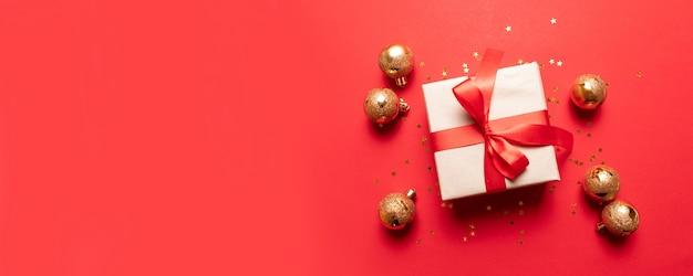 Composition créative avec boîte présente rouge, rubans, petites et grandes boules en or rouge, décorations de fêtes sur fond rouge.