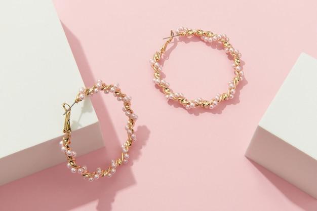 Composition créative avec boucles d'oreilles sur fond rose bijoux tendance dans un style minimaliste