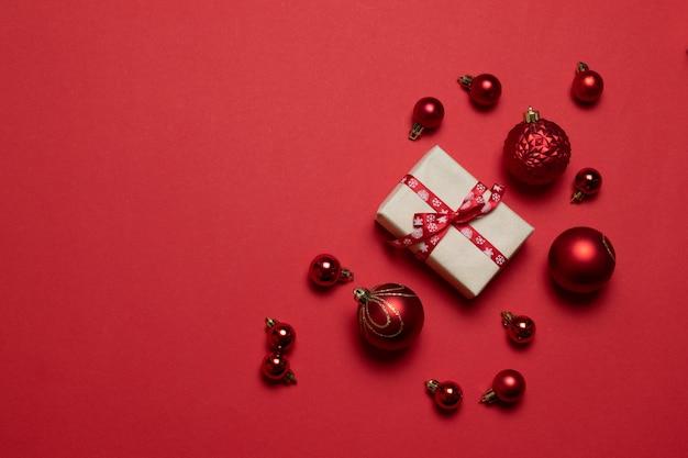 Composition créative avec des cadeaux ou présente des boîtes avec des arcs rouges, des boules rouges sur fond rouge.