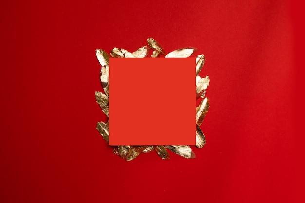 Composition créative avec cadre de feuille rouge avec des feuilles d'or sur fond rouge.