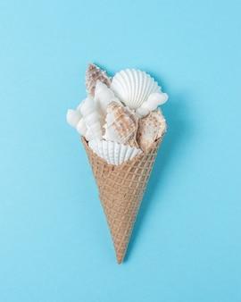 Composition créative avec des coquillages et cornet de crème glacée sur fond bleu pastel.