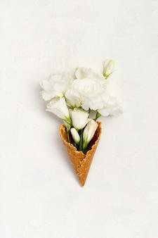 Composition créative avec cornet de crème glacée et fleurs sur fond blanc. carte de voeux de fête des mères anniversaire womans day.