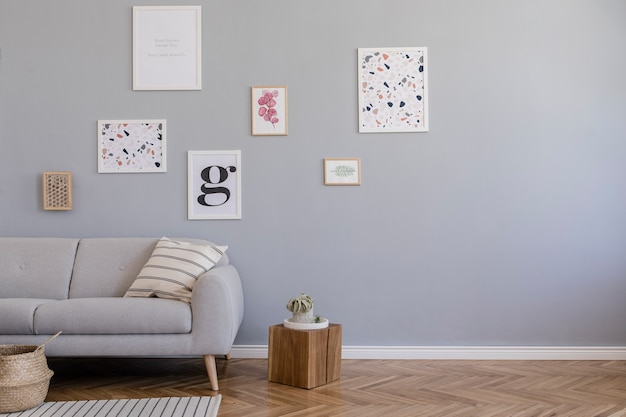 Composition créative de design d'intérieur de salon scandinave élégant avec cadres d'affiches, canapé, commode en bois, chaise, plantes et accessoires. murs neutres, parquet au sol.