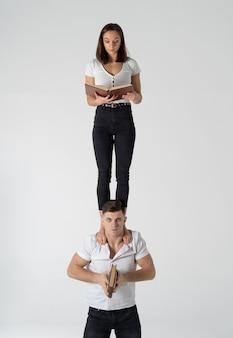 Composition créative de femme debout sur les épaules de l'homme et livre de lecture. concept d'éducation et d'auto-amélioration.