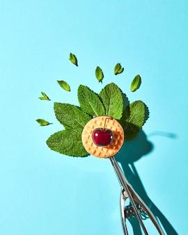 Composition créative de feuilles de menthe dans la cuillère en métal pour crème glacée et biscuit à la cerise sur fond de verre bleu avec des ombres. style moderne de la nourriture, vue de dessus.