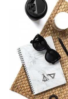 Composition créative avec lunettes de soleil, planificateur, cosmétiques et serviette en paille sur fond blanc
