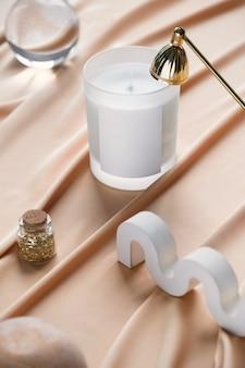 Composition créative de nature morte avec bougie de soja sur fond pastel crémeux, extincteur et accessoires élégants