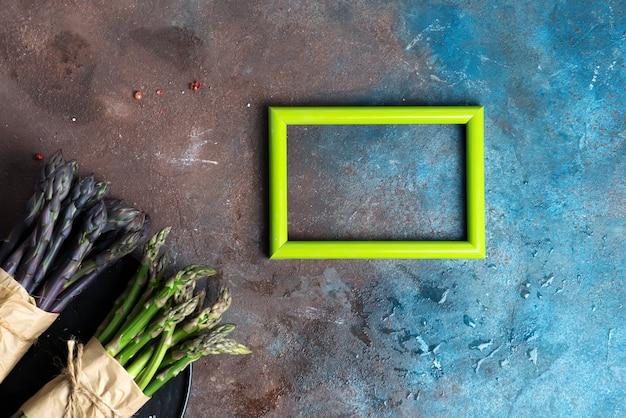 Composition créative à partir d'un cadre photo et de grappes d'asperges biologiques fraîches sur un fond de pierre sombre.