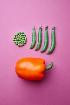 Composition créative à partir de grains de pois verts sous la forme d'un cercle et plein de gousses fermées et de poivron rouge sur fond rose. mise à plat. concept alimentaire.