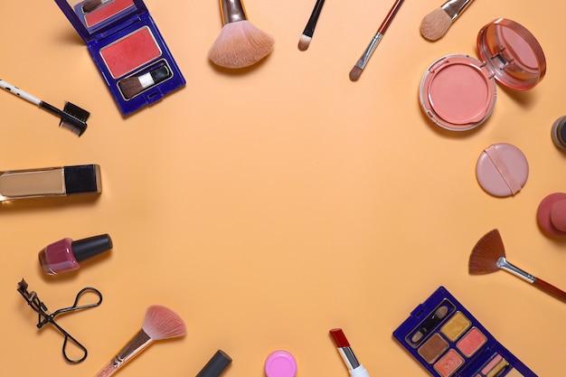 Composition créative à plat de l'ensemble de maquillage avec espace de copie au centre