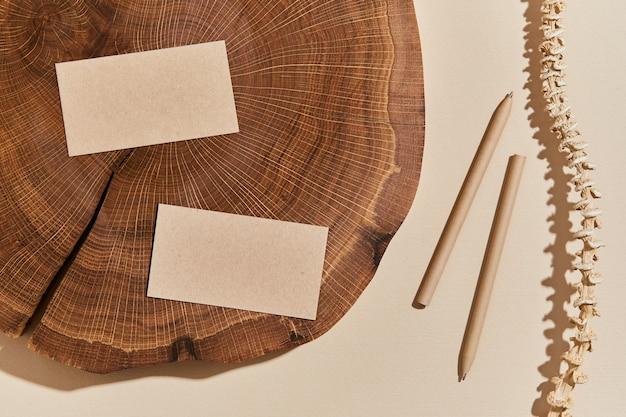 Composition créative à plat avec maquettes de cartes de visite, bois, matériaux naturels et accessoires. couleurs neutres, vue de dessus, modèle.