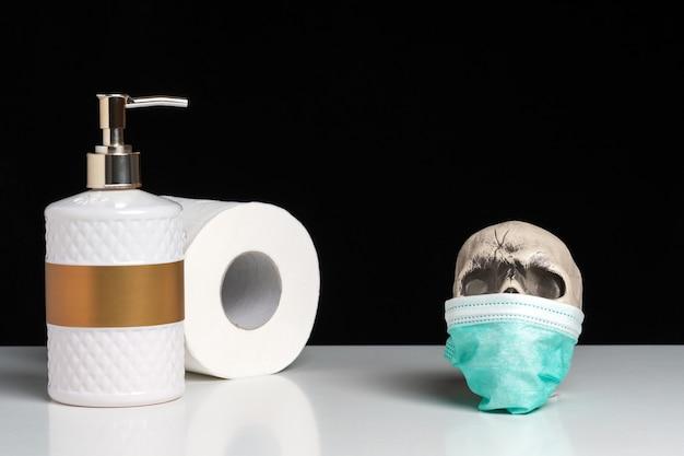 Composition créative avec un savon pour les mains et du papier toilette et un crâne sur un tableau blanc.