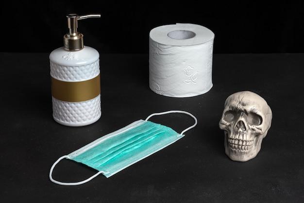 Composition créative avec un savon pour les mains et du papier toilette et un crâne sur un tableau noir.