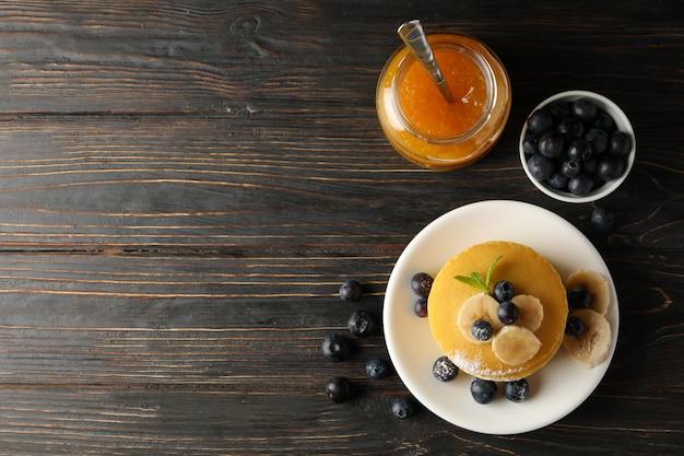 Composition avec crêpes, banane, myrtille et confiture sur table en bois, vue de dessus