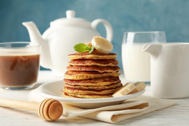 Composition avec crêpes, lait et boisson au cacao sur table en bois. petit déjeuner sucré