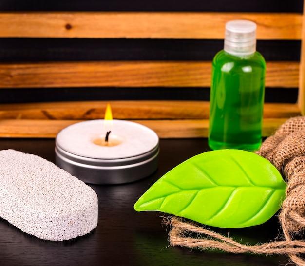 Composition de cure thermale sur table en bois. savon, bougie, bouteille d'huile, pierre ponce et toile de jute sur tableau noir.