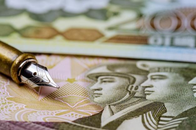 La composition dans les divers billets d'argent a gagné la monnaie nord-coréenne sur un stylo pour l'écriture