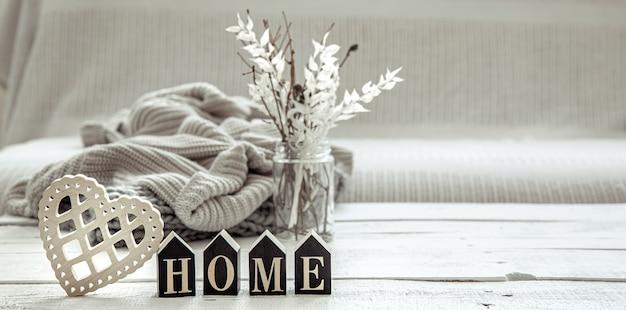 Composition dans le style hygge avec le mot en bois home, des détails de décoration et un élément tricoté