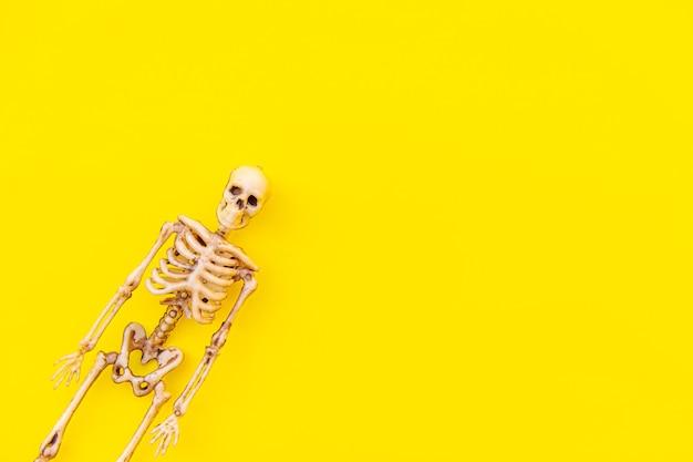 Composition de décorations minimales d'halloween avec un monstre squelette effrayant isolé sur fond jaune...
