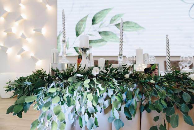 Une composition décorative de feuilles vertes et de bougies d'argent dans une salle lumineuse