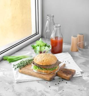 Composition avec un délicieux burger fait maison, du jus de tomate et des légumes sur le rebord de la fenêtre.