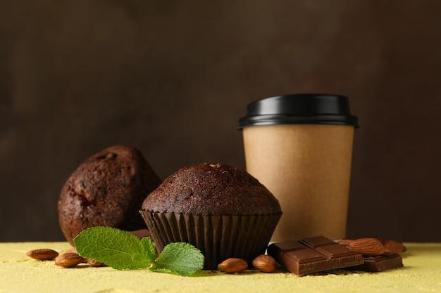 Composition avec de délicieux muffins et tasse en papier sur tableau jaune